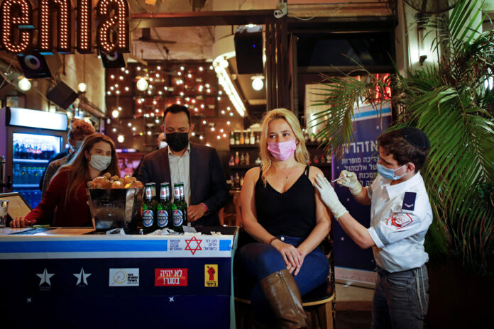 A woman receives a vaccination against COVID-19 as part of a Tel Aviv municipality initiative offering a free drink at a bar to residents getting the shot