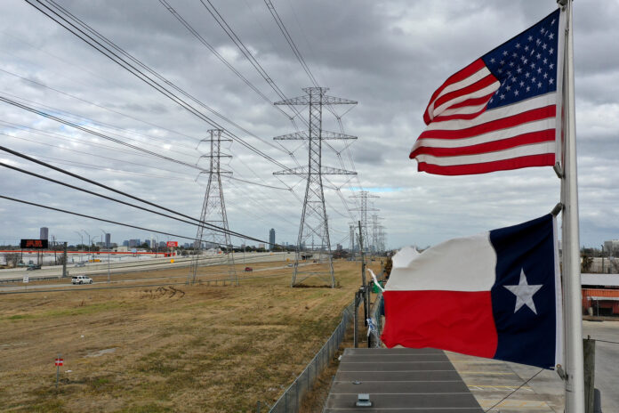 The U.S. and Texas flags fly in front of high voltage transmission towers in Houston, Texas.
