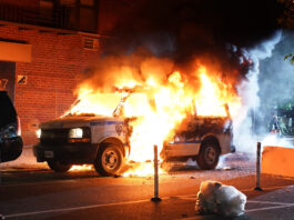 An NYPD officer monitors the crowd as an NYPD van burns in the background that was set on fire during a chaotic protest over the death of George Floyd in NYC last May.